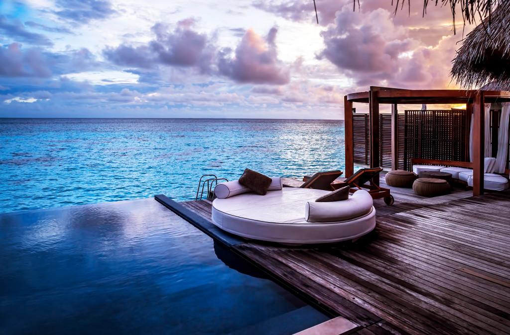 Luxury beach resort, bungalow near endless pool over sea sunset,