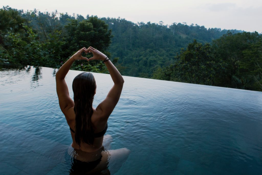 A woman meditating in an infinity pool overlooking a forest. Photo by Jon Flobrant on Unsplash.