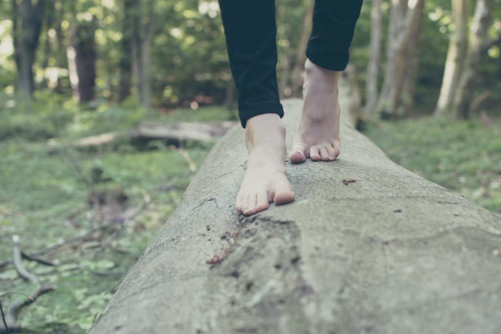 Woman walking on log. Photo by Michal Parzuchowsk on Unsplash.