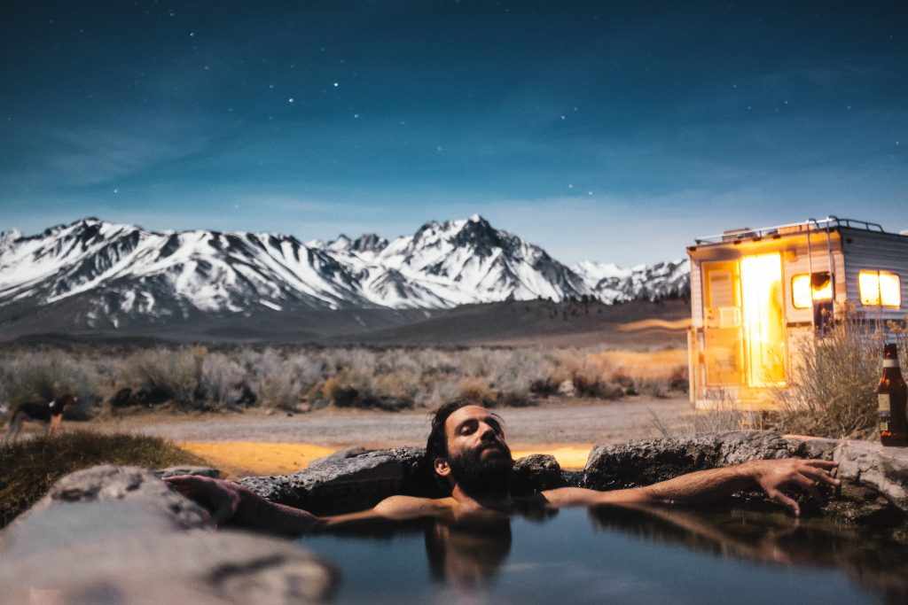 Mountain man relaxing in a hot tub during a snow retreat.